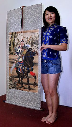Sandy holding a Guan Gong wall scroll