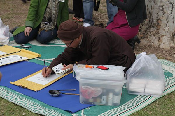 Chat Nguyen paints calligraphy in the park