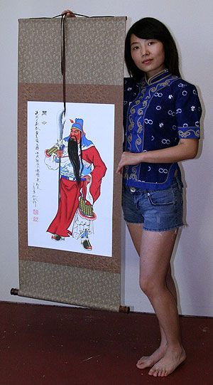 Sandy holding a Jin Bin Guan Gong wall scroll