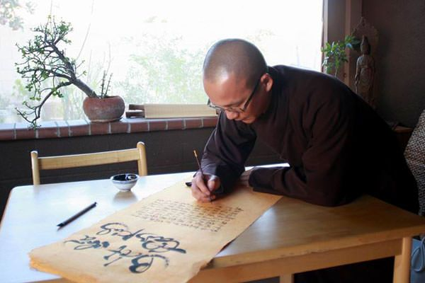 Chat Nguyen paints his Buddhist calligraphy at the temple