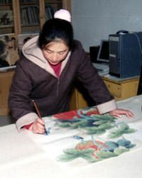 Qin Xia works on another one of her paintings
